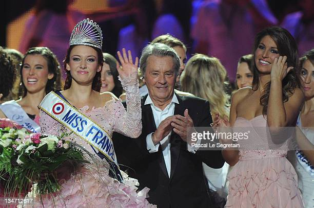 Miss France 2012 Delphine Wespiser waves as Alain Delon and Laury Thilleman stand on stage on December 3 2011 in Brest France