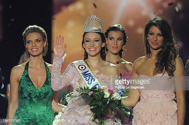 Miss France 2012 Delphine Wespiser waves as Sylvie Tellier director of the Miss France competition and Laury Thilleman stand on stage on December 3...
