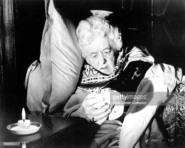 Miss Jane Marple played by English actress Margaret Rutherford wakes up to an alarm clock in 'Murder At The Gallop' directed by George Pollock 1963