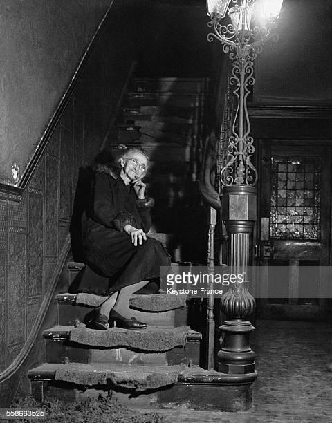 Miss Louise Laumonier dans les escaliers de la maison qu'elle habite depuis plus de 80 ans et qu'elle doit maintenant céder le 10 février 1956 à...