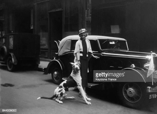 Miss Paris photographiée avec son chien devant sa voiture à Paris France en juillet 1935