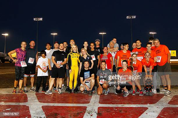 Miss Sprint Cup Kim Coon and Kurt Busch take part in his 'BuschWhacked' Mud Run at Texas Motor Speedway Dirt Track on October 31 2013 in Fort Worth...