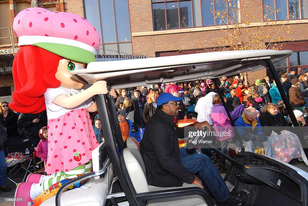 Miss Strawberry Shortcake gets a ride on the back of a golf cart to the staging area at America's Thanksgiving Day Parade at Woodward Avenue on November 22, 2012 in Detroit, Michigan.