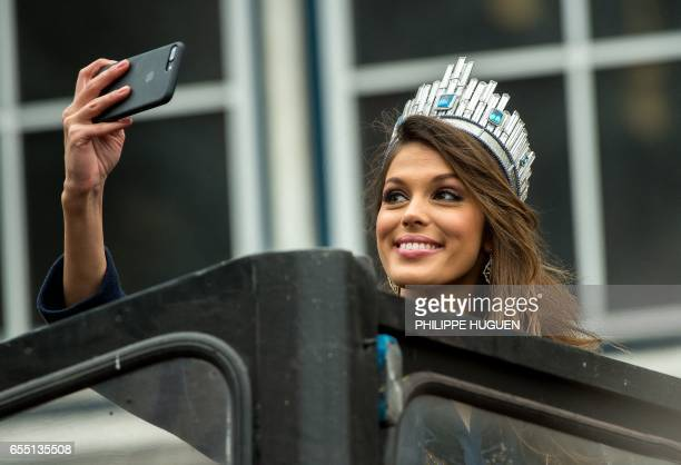 Miss Univers French Iris Mittenaere takes a selfie as she salutes the crowd upon her arrival to visit Lille northern France on March 19 2017 / AFP...