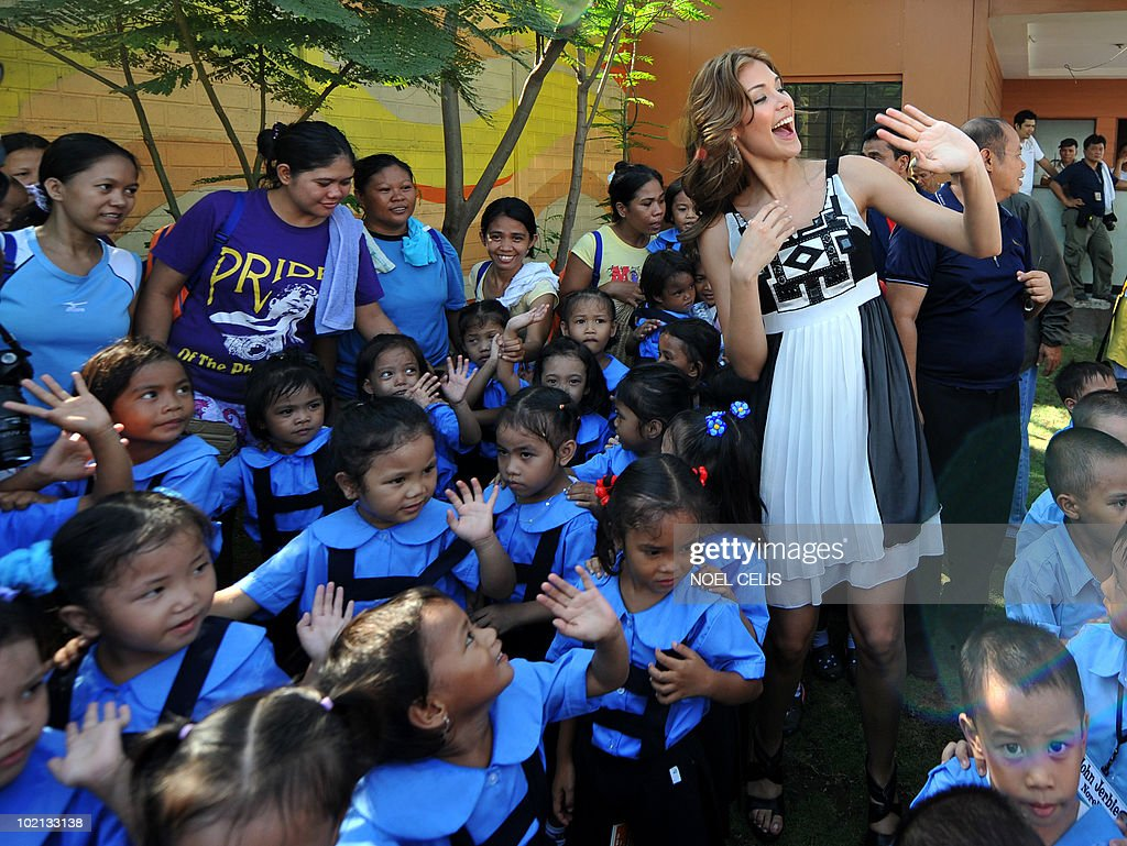 Miss Universe 2008 Dayana Mendoza (R) interacts with elementary students from Tondo, a slum area in Manila on June 16, 2010. The Venezuelan beauty was named Smartmatic's 'Ambassador of Transparency' and flew to Manila for a three day tour to join the celebrations over the success of the automated elections.