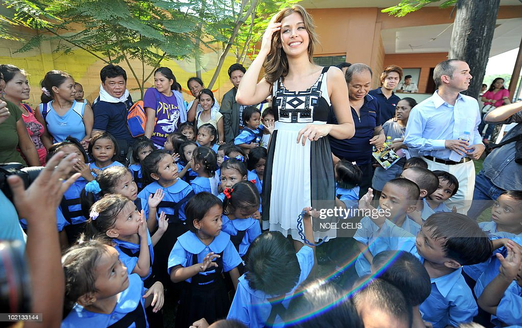 Miss Universe 2008 Dayana Mendoza (C) interacts with elementary students from Tondo, a slum area in Manila on June 16, 2010. The Venezuelan beauty was named Smartmatic's 'Ambassador of Transparency' and flew to Manila for a three day tour to join the celebrations over the success of the automated elections.