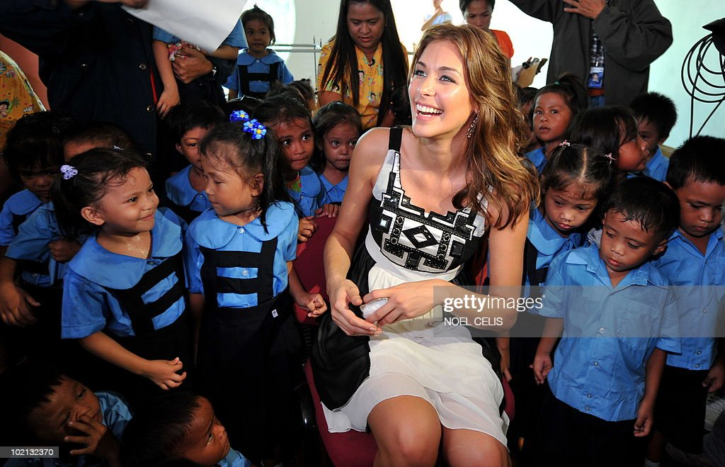 Miss Universe 2008 Dayana Mendoza sits beside the elementary students from Tondo, a slum area in Manila on June 16, 2010. The Venezuelan beauty was named Smartmatic's 'Ambassador of Transparency' and flew to Manila for a three day tour to join the celebrations over the success of the automated elections.