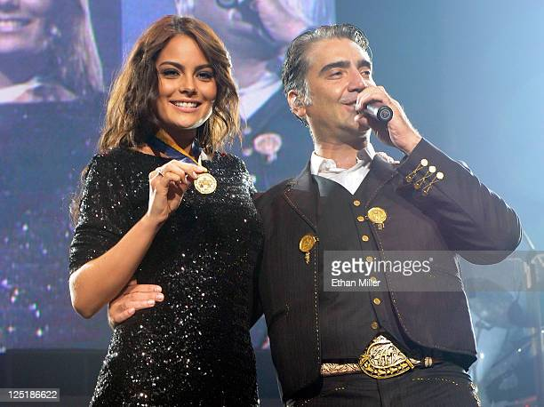 Miss Universe 2010 Jimena Navarrete displays a medallion she received from singer Alejandro Fernandez as he performs during his Dos Mundos tour at...