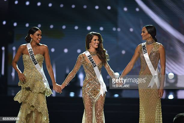 Miss Universe candidates Andrea Tovar of Colombia Iris Mittenaere of France and Raquel Pelissier of Haiti stand on stage holding hands as they wait...
