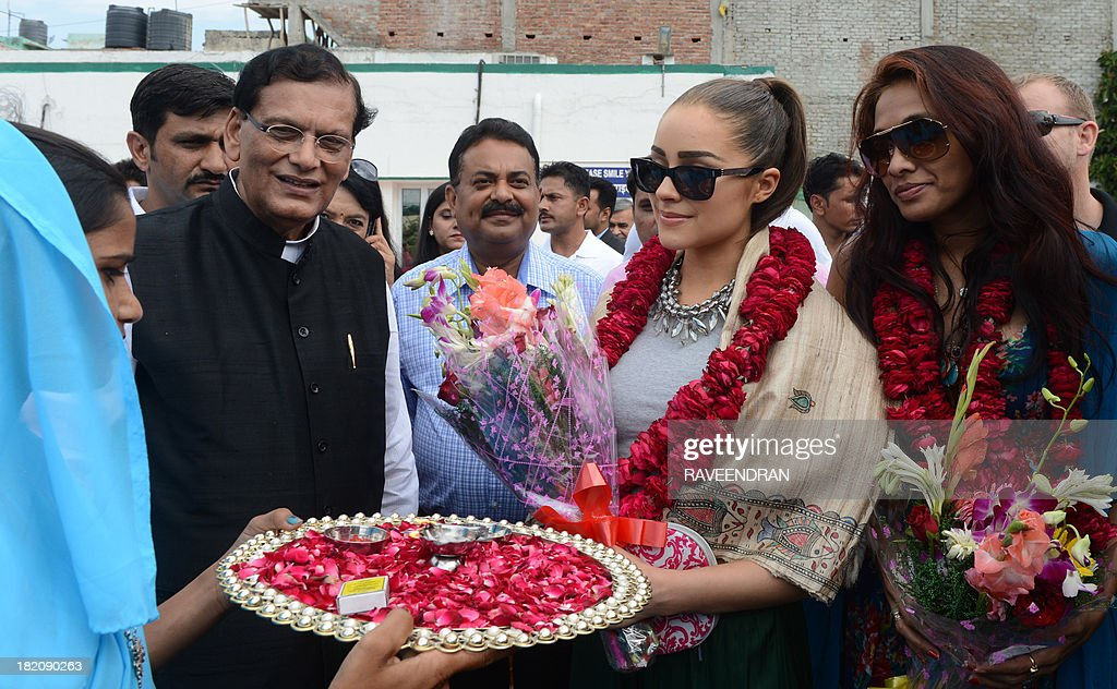 Miss Universe, Olivia Frances Culpo from United States (2R), accompanied by the founder/chairman of Sulabh International, Bindeshwari Pathak (2L), is welcomed with rose petals by a former manual scavenger during her visit to Sulabh International Social Service Organisation in New Delhi on September 28, 2013. Sulabh International, which counts 50,000 volunteers, is a social service organization which works to promote human rights, environmental sanitation, non-conventional sources of energy, waste management and social reforms through education. AFP PHOTO/RAVEENDRAN