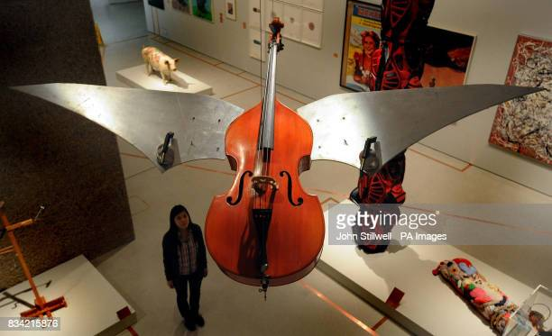 Miss WingSie Chan a Curatorial Intern at the Barbican Art Gallery in the City of London studies the Flying double Bass by Ben Patterson an exhibit in...