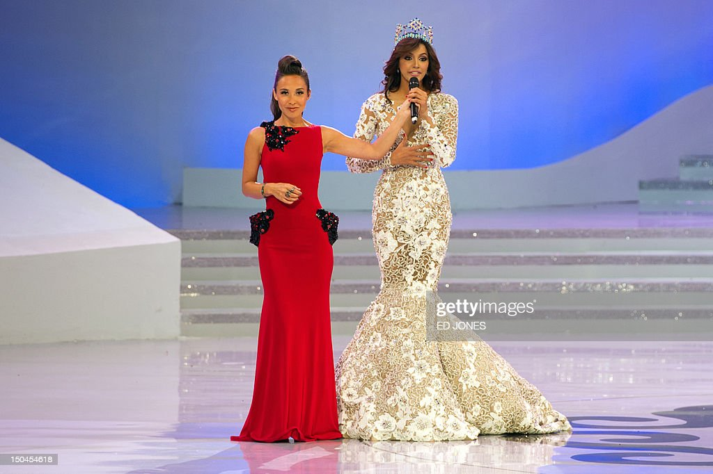 Miss World 2012 host Mylene Klass (L) of Britain holds a microphone for Miss World 2011 winner Ivian Sarcos of Venezuela during the pageant's final ceremony at Dongsheng Stadium in the inner Mongolian city of Ordos on August 18, 2012. China's Yu Wenxia defeated more than 100 other hopefuls at the glittering ceremony held in the Chinese mining city of Ordos, on the edge of the Gobi desert. AFP PHOTO / Ed Jones