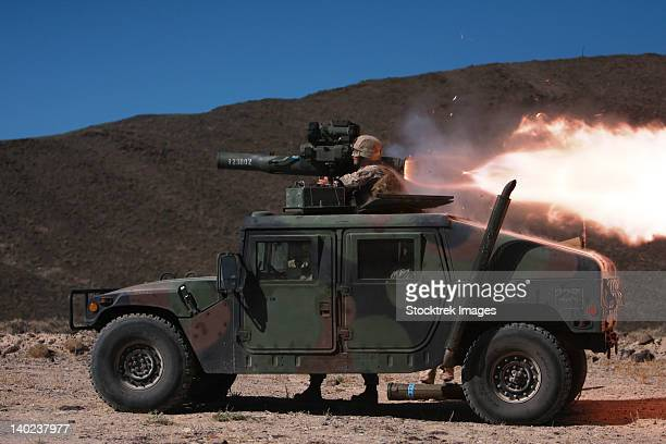 A missileman firing a BGM-71 TOW missile atop a humvee.