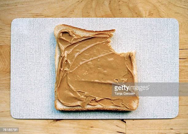 A missing bite from a slice of bread with peanut butter