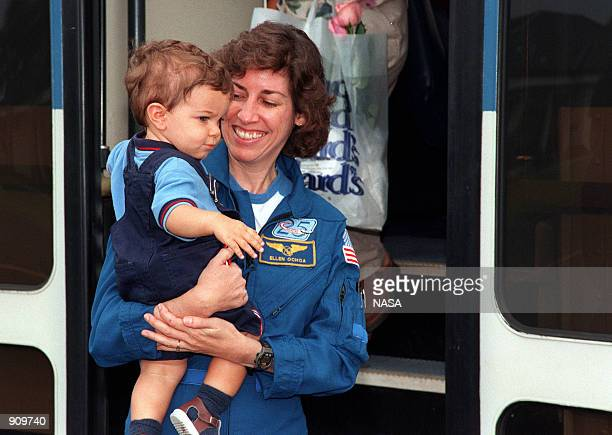 Mission Specialist Ellen Ochoa holds her son Wilson MilesOchoa as she steps off the bus at the Cape Canaveral Air Station Skid Strip June 7 1999 The...