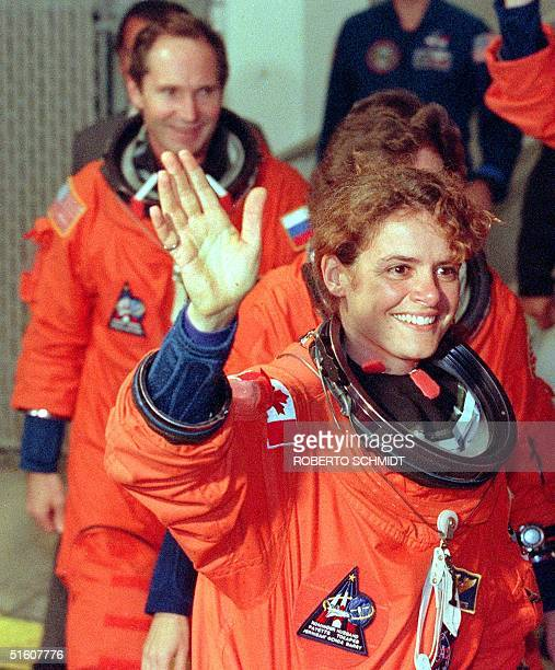 Mission Specialist Julie PaYette of the Canadian Space Agency waves as she walks out of the crew quarters building at the Kennedy Space Center FL...