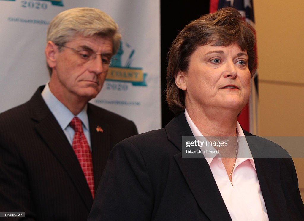 Mississipi Gov. Phil Bryant, left, listens as the state's Department of Environmental Quality director, Trudy Fisher, speaks at a news conference at the Mississippi Coast Convention Center in Biloxi, Mississippi, on Wednesday, August 21, 2012, announcing the creation of GoCoast 2020. Fisher will lead the advisory group, which will develop a plan for recovery and restoration from the Deepwater Horizon oil rig explosion in the Gulf of Mexico.