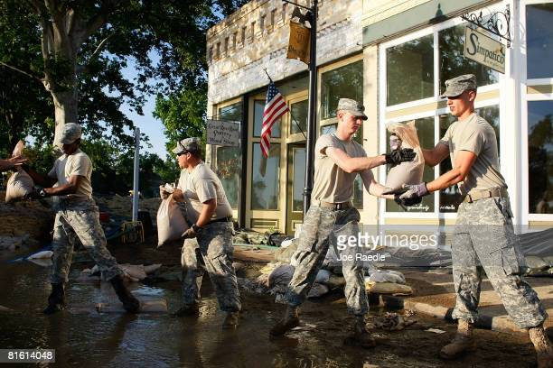 Missouri Army National Guard soldiers continue to stack sandbags as they help keep the flooding Mississippi River from inundating business June 18...