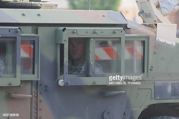 Missouri National Guard personnel looks outside the window of a military vehicle prior to offering location support for law enforcement at the...