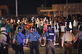 Missouri State Highway Patrol officers listen to taunts from demonstrators during a protest over the death of Michael Williams on August 15 2014 in...