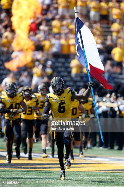 Missouri Tigers wide receiver J'Mon Moore carries a Texas state flag as he leads his team onto the field prior to a football game against the...