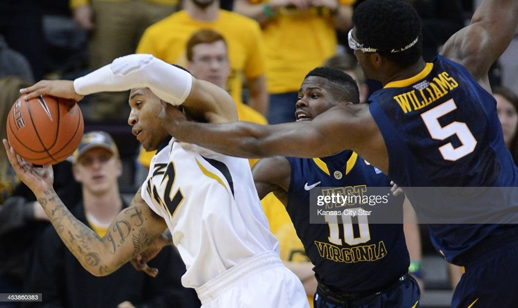 Missouri's Jabari Brown, left, pulls a rebound away from West Virginia's Eron Harris (1) and Devin Williams (5) during the first half at Mizzou Arena in Columbia, Mo., on Thursday, Dec. 5, 2013. Missouri won, 80-71.