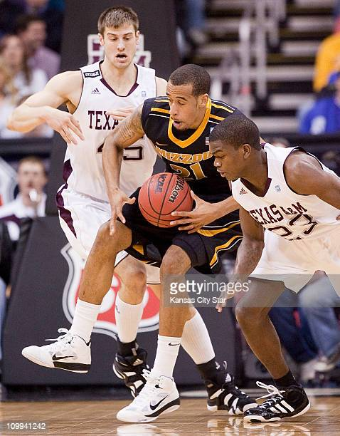 Missouri's Laurence Bowers middle tries to regain his balance while being surrounded by Texas AM's Nathan Walkup and Naji Hibbert during the...