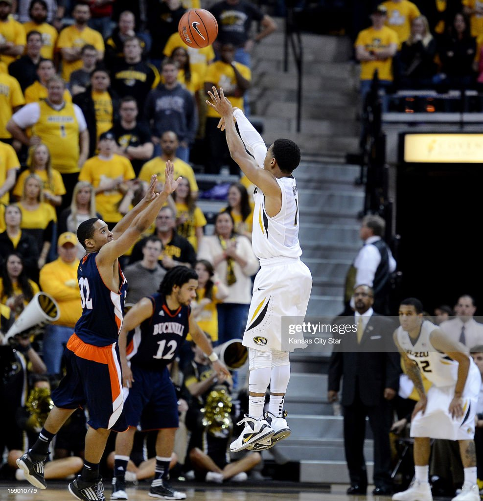 Missouri's Phil Pressey has the attention of head coach Frank Haith and teammate Jabari Brown, right, as he puts up a three-pointer over Bucknell's Ryan Frazier in the second half at Mizzou Arena in Columbia, Missouri, Saturday, January 5, 2013. Missouri beat Bucknell, 66-64.