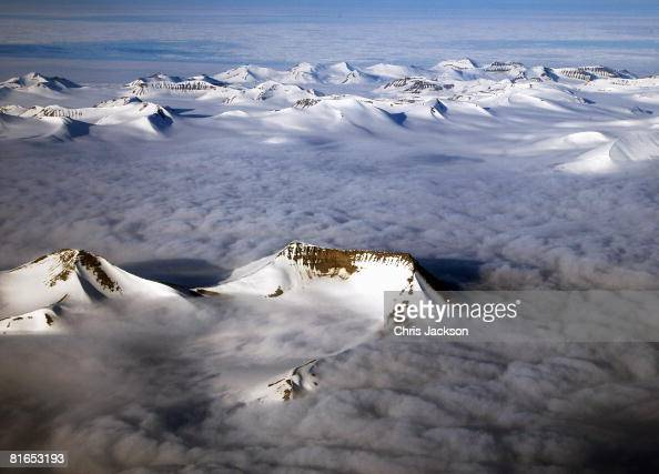 Mist encircles mountain peaks as the midnight sun reflects off the face of ridges on the West Coast of Spitsbergen early in the morning of Midsummer...