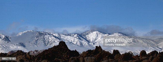 Mist rising from snow covered mountains : Stock Photo