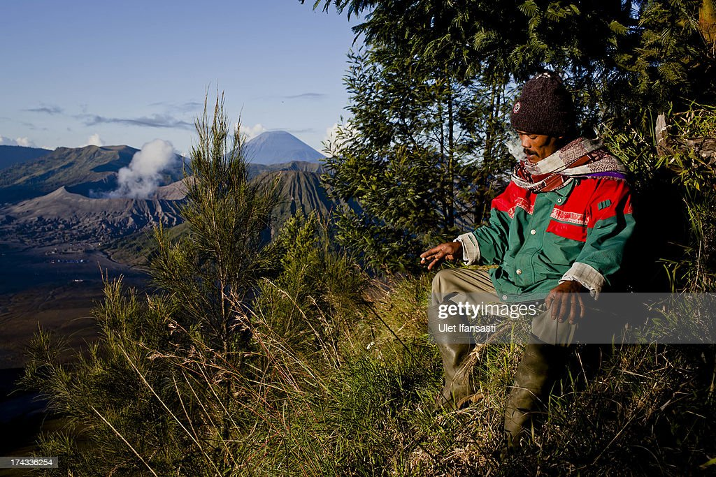 Mistingal, sits as he takes a break with Mount Bromo, Mount Rinjani, the location of the Tenggerese villages where the Tenggerese Hindu Yadnya Kasada Festival is held, in the background, on July 23, 2013 in Probolinggo, Indonesia. The festival is the main festival of the Tenggerese people and lasts about a month. On the fourteenth day, the Tenggerese make the journey to Mount Bromo to make offerings of rice, fruits, vegetables, flowers and livestock to the mountain gods by throwing them into the volcano's caldera. The origin of the festival lies in the 15th century when a princess named Roro Anteng started the principality of Tengger with her husband Joko Seger, and the childless couple asked the mountain Gods for help in bearing children. The legend says the Gods granted them 24 children but on the provision that the 25th must be tossed into the volcano in sacrifice. The 25th child, Kesuma, was finally sacrificed in this way after initial refusal, and the tradition of throwing sacrifices into the caldera to appease the mountain Gods continues today.