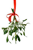 Close-up of a bunch of mistletoe (Viscum album) with berries, hanging from ared ribbon and isolated on a white background.