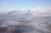 A misty morning aerial landscape with two power stations in the background.