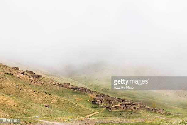 Misty landscape view of stone houses on hillside, Oukaimeden ski resort, Marrakech, Morocco