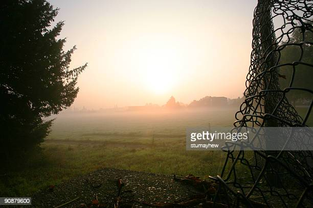 Misty  sunrise and wire fence
