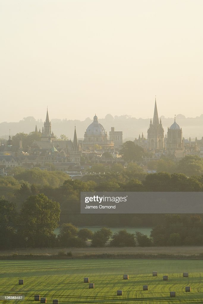 A misty view over the fields toward the Oxford skyline at sunrise.