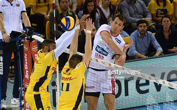 Mitar Djuric of Diatec Trentino spikes the ball against to Matteo Piano and Earvin Ngapeth of DHL Modena during the Italian Volleyball Supercup at...