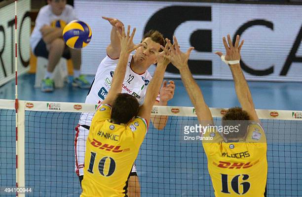 Mitar Djuric of Diatec Trentino spikes the ball against to Milos Nikic and and Lucas Saatkamp of DHL Modena during the Italian Volleyball Supercup at...