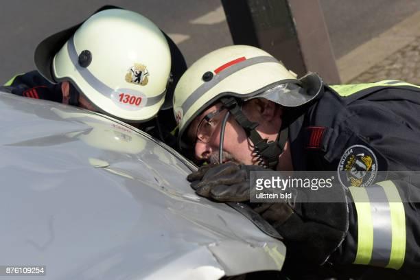 Mitarbeiter der Berliner Feuerwehr begutachten ein Fahrzeug nach einem Verkehrsunfall