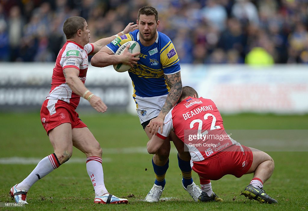 Mitch Achurch of Leeds is tacked by Travis Burns and Rich Beaumont of Hull KR during the Super League match between Hull Kingston Rovers and Leeds Rhinos at Craven Park Stadium on April 28, 2013 in Hull, England.