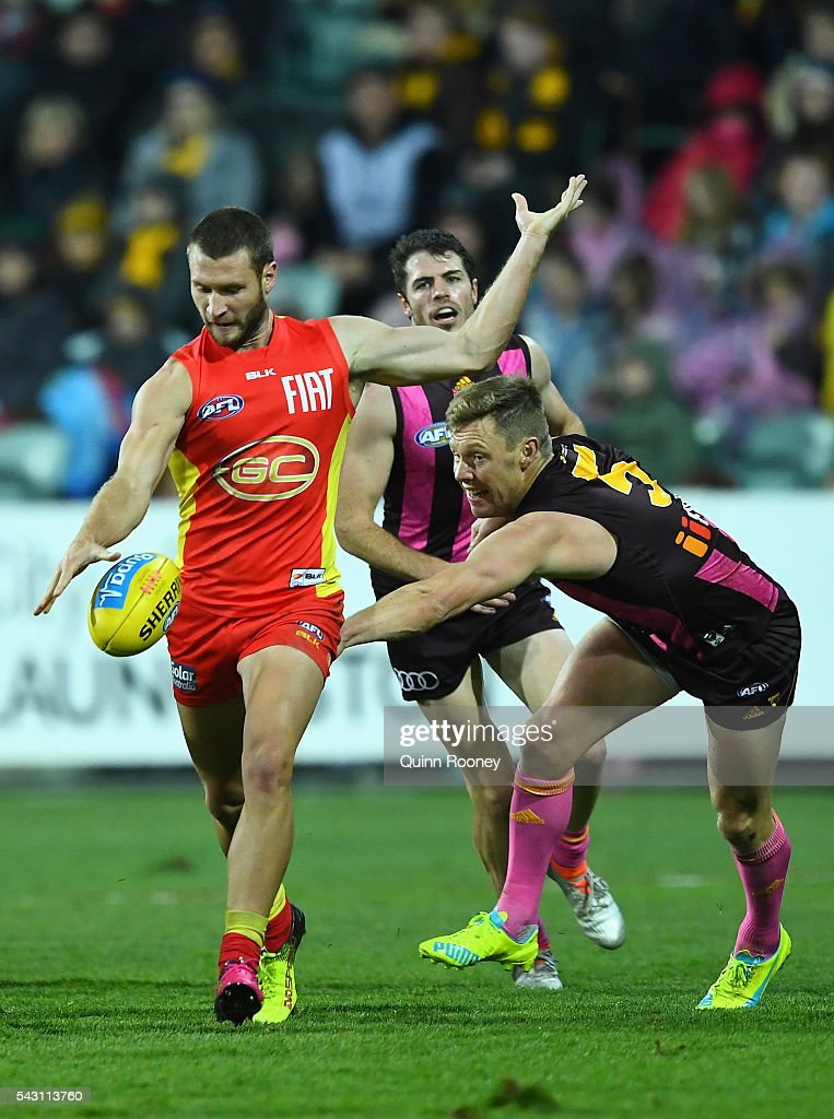 Mitch Hallahan of the Suns kicks whilst being tackled by Sam Mitchell of the Hawks during the round 14 AFL match between the Hawthorn Hawks and the Gold Coast Suns at Aurora Stadium on June 26, 2016 in Launceston, Australia.