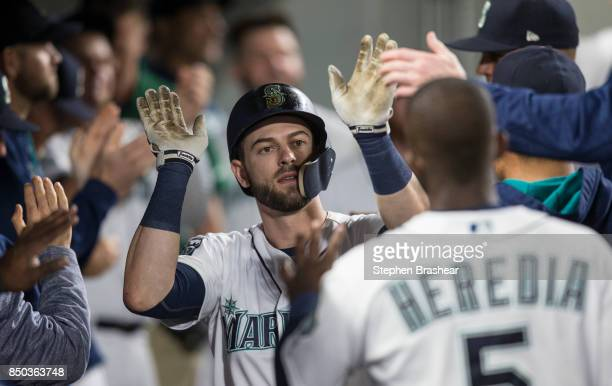 Mitch Haniger of the Seattle Mariners is congratulated by teammates in the dugout after hitting a solo home run off of starting pitcher Andrew...
