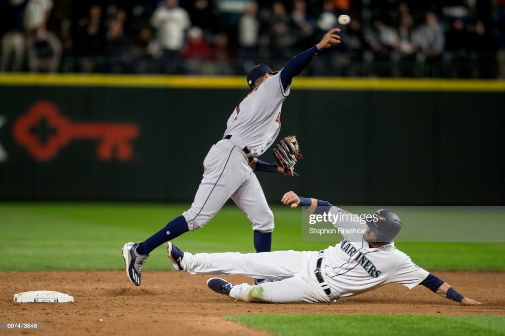 Mitch Haniger #17 of the Seattle Mariners tries to break up a double play as shortstop Carlos Correa #1 of the Houston Astros throws to first base during the ninth inning of game at Safeco Field on April 11, 2017 in Seattle, Washington. The Astros won the game 7-5. Haniger was out at first and Robinson Cano #22 of the Seattle Mariners was safe at first on the fielder's choice.