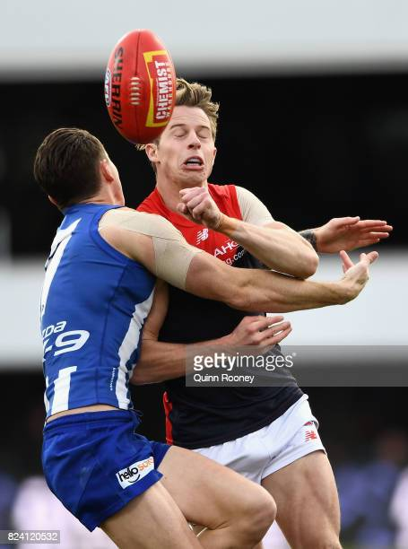 Mitch Hannan of the Demons handballs whilst being tackled by Aaron Mullett of the Kangaroos during the round 19 AFL match between the North Melbourne...