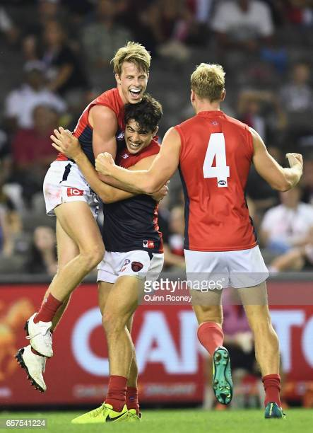 Mitch Hannan of the Demons is congratulated by Christian Petracca and Jack Watts of the Demons during the round one AFL match between the St Kilda...