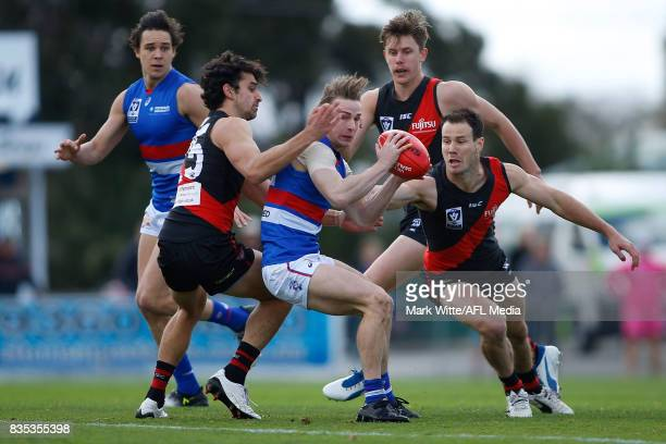 Mitch Honeychurch of Footscray Bulldogs gets through the pack of Alex Morgan and Matt Dea of Essendon Bombers during the round 18 VFL match between...