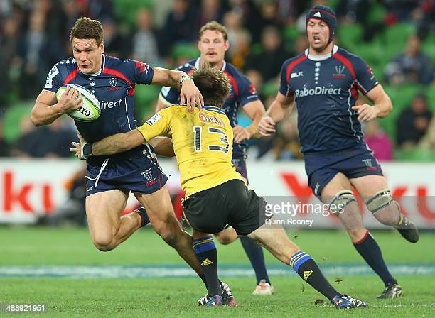 Mitch Inman of the Rebels is tackled by Conrad Smith of the Hurricanes during the round 13 Super Rugby match between the Rebels and the Hurricanes at...