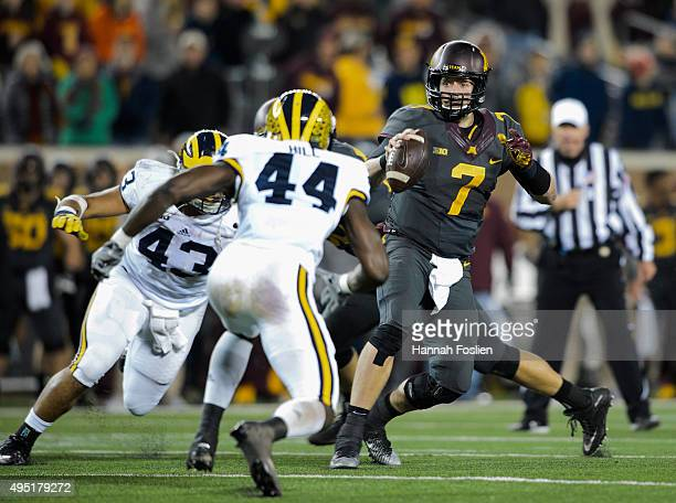 Mitch Leidner of the Minnesota Golden Gophers looks to pass the ball under pressure from Chris Wormley and Delano Hill of the Michigan Wolverines...