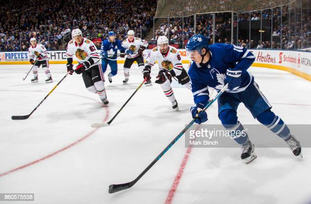 Mitch Marner of the Toronto Maple Leafs carries the puck past Michal Kempny and Tanner Kero of the Chicago Blackhawks during the first period October...