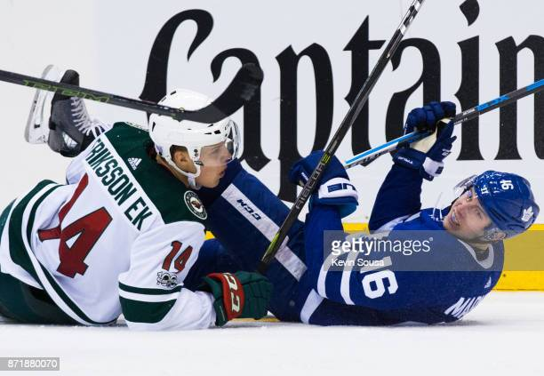 Mitch Marner of the Toronto Maple Leafs gets tangled up with Joel Eriksson Ek of the Minnesota Wild during the third period at the Air Canada Centre...